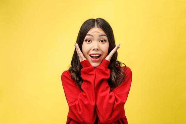 La ragazza asiatica felice del ritratto è sorpresa che sia eccitata. studio del fondo giallo.