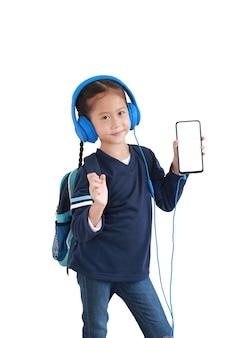 La ragazza asiatica felice del ragazzino del ritratto gode con lo smartphone e le cuffie isolate su bianco