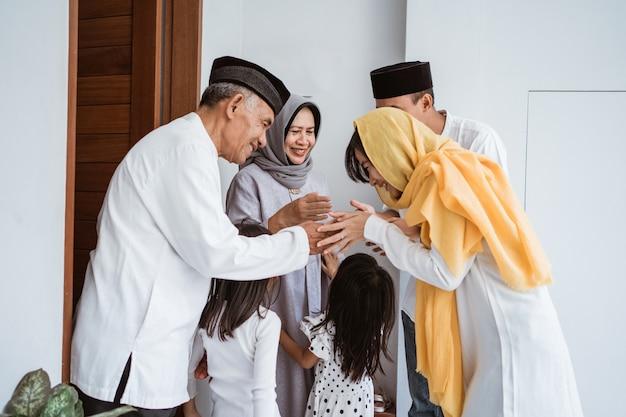 Ritratto della famiglia musulmana asiatica felice che visita i nonni su ramadan kareem. popolo indonesiano che celebra eid mubarak