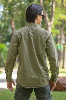 Ritratto di felice giovane asiatico in camicia a maniche lunghe e pantaloni verdi in piedi nel parco