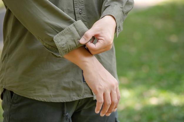 Ritratto del giovane asiatico felice in camicia a maniche lunghe e mutanda verde in piedi nel parco
