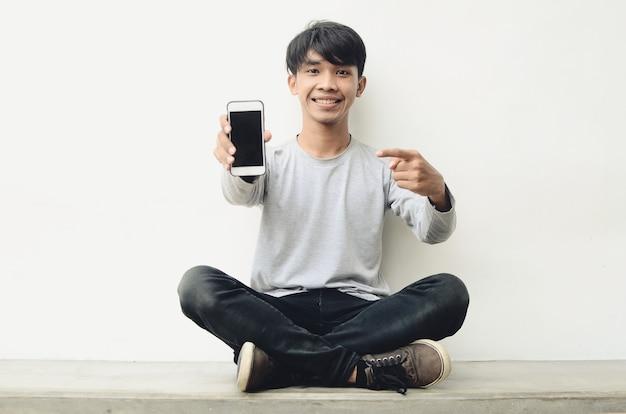 Ritratto di una giovinezza asiatica felice che indica un telefono cellulare