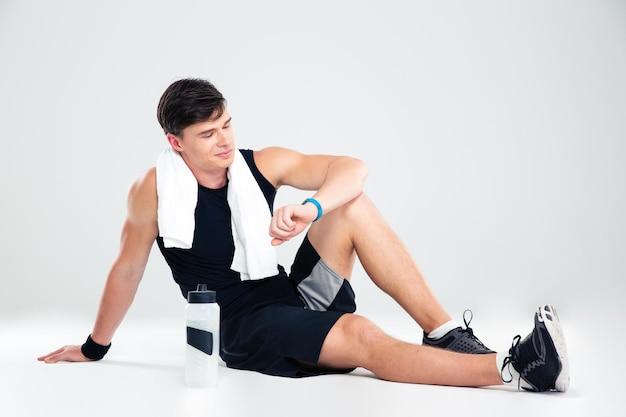 Ritratto di un uomo atletico felice che riposa sul pavimento e che guarda il fitness tracker isolato