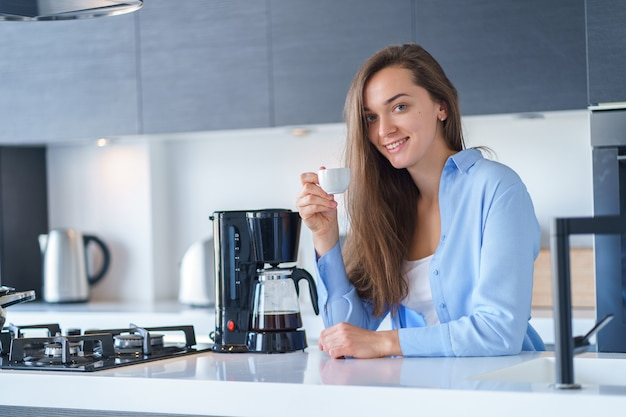 Ritratto della femmina attraente felice che beve caffè aromatico fresco dopo la preparazione del caffè facendo uso della macchinetta del caffè nella cucina a casa. frullatore per caffè ed elettrodomestici da cucina per bevande calde