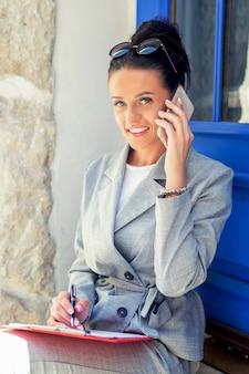Ritratto di felice attraente giovane imprenditrice parlando al telefono intelligente vicino alla porta all'aperto.