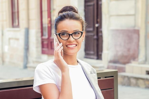 Ritratto di felice attraente giovane imprenditrice indossando occhiali da sole parlando al telefono intelligente seduto sulla panchina all'aperto.