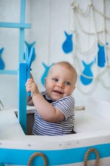 Ritratto di un neonato felice con gli occhi azzurri che tiene il volante su una parete con uno scenario di mare
