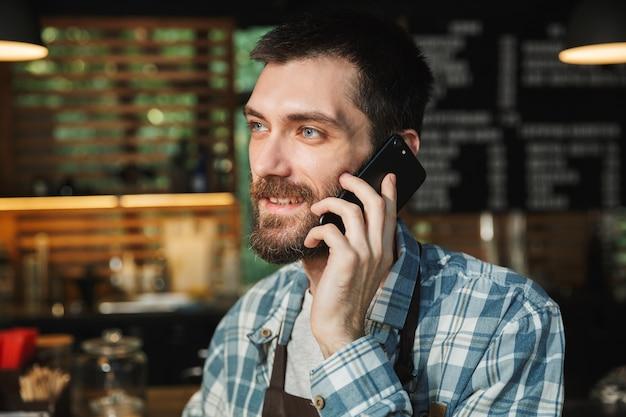 Ritratto di un barista felice che indossa un grembiule che sorride e parla al cellulare in un caffè di strada o in un caffè all'aperto