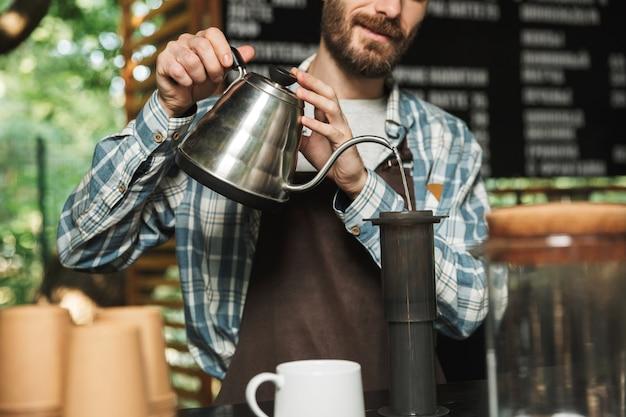 Ritratto di un barista felice che indossa un grembiule che fa il caffè mentre si lavora in un caffè di strada o in un caffè all'aperto