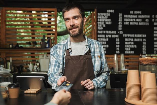 Ritratto di felice barista uomo che indossa grembiule prendendo la carta di credito dal cliente mentre si lavora in street cafe o coffeehouse outdoor