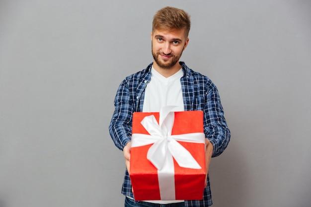 Ritratto di un uomo barbuto felice che dà una confezione regalo sul davanti sopra il muro grigio