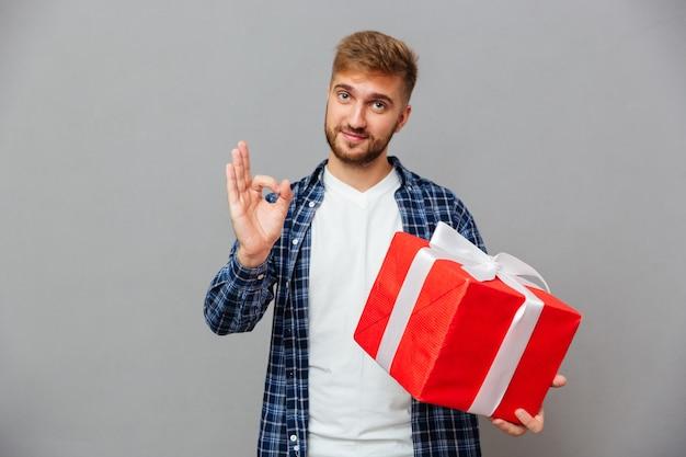 Ritratto di un uomo barbuto felice che tiene il contenitore di regalo e che mostra il gesto giusto sopra il muro grigio