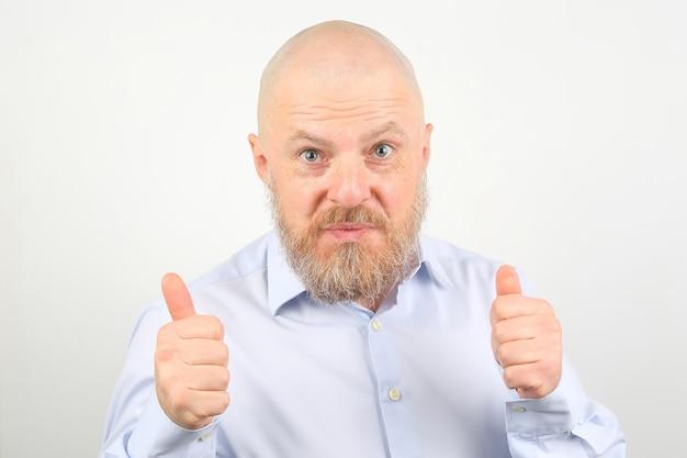 Ritratto di un uomo barbuto felice in una camicia con le braccia alzate