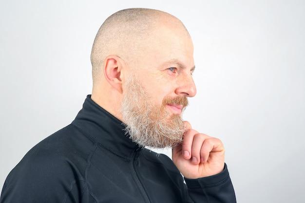 Ritratto di un uomo barbuto felice in luci soffuse