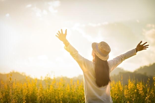Ritratto di felice giovane e felice felice relax nel parco. modello femminile gioiosa che respira aria fresca all'aperto e godendo odore in una primavera di fiori o giardino estivo, tono d'annata