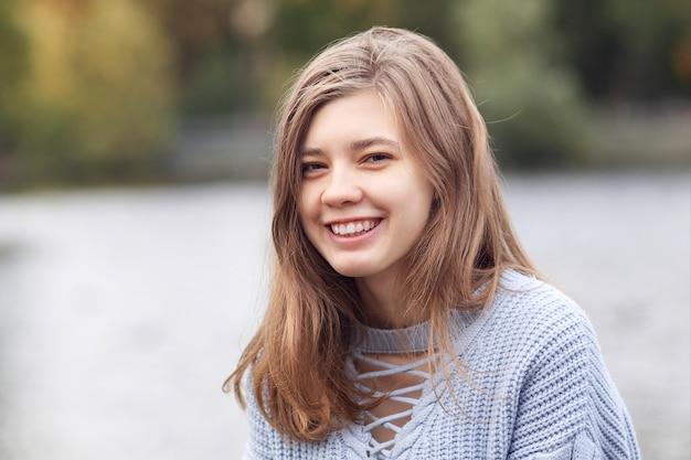 Ritratto di felice bella giovane donna positiva, adolescente sorridente, ridendo in maglione nel parco
