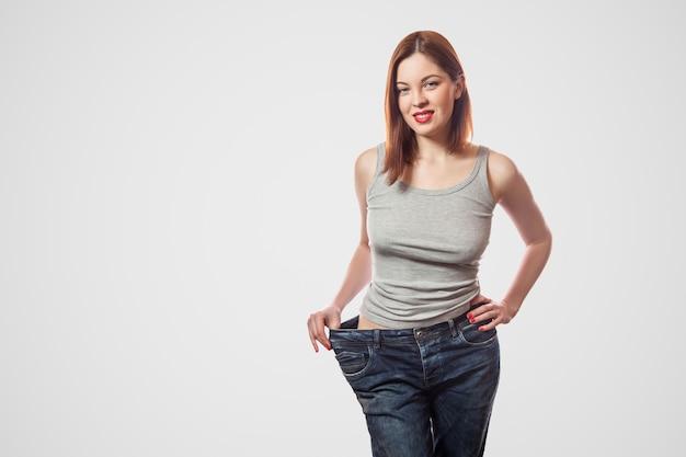 Ritratto di felice bella vita sottile di giovane donna in jeans grandi e top grigio che mostra perdita di peso di successo, coperta, studio girato, isolato su sfondo grigio chiaro, concetto di dieta.