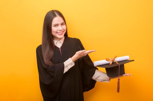 Il ritratto di bella donna felice in abito di graduazione sta tenendo il certificato di istruzione su fondo giallo