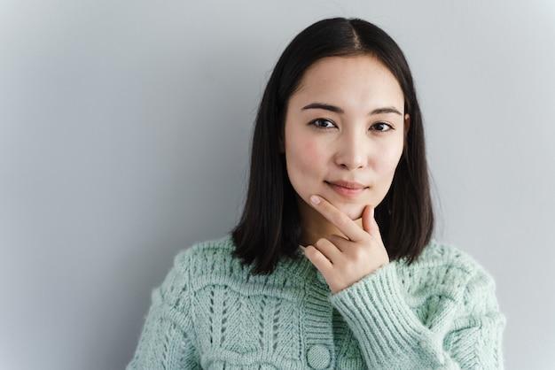Ritratto felice bella donna pensando guardando in alto isolato muro grigio sfondo con copia spazio