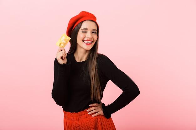 Ritratto di una bella giovane donna felice che indossa in piedi berretto rosso isolato su sfondo rosa, tenendo la carta di credito in plastica