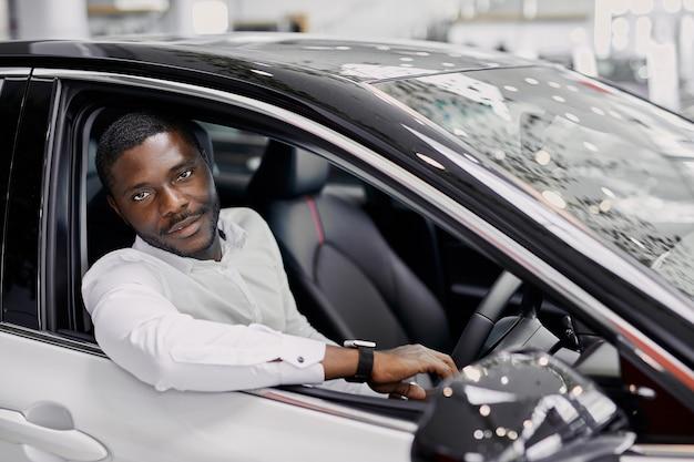 Ritratto di uomo d'affari nero felice all'interno di auto di lusso