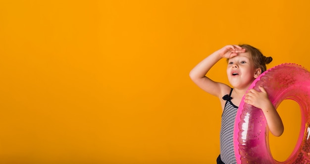 Ritratto di una ragazza bionda felice in un costume da bagno a strisce che tiene un cerchio gonfiabile rosa su una superficie gialla con spazio per testo