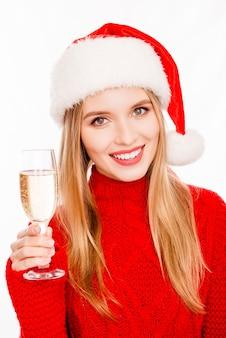 Ritratto di felice bionda in cappello di babbo natale che celebra il natale con shampagne