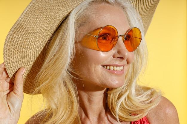 Ritratto di donna bionda felice in occhiali da sole e cappello di paglia che sorride da parte aggiustando il suo cappello mentre