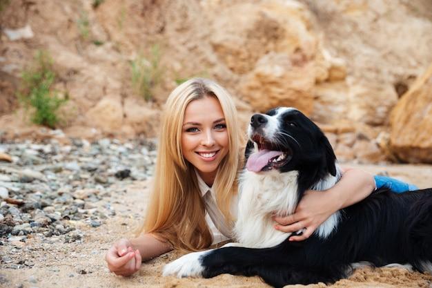 Ritratto di giovane donna bionda felice che abbraccia il suo cane sulla spiaggia