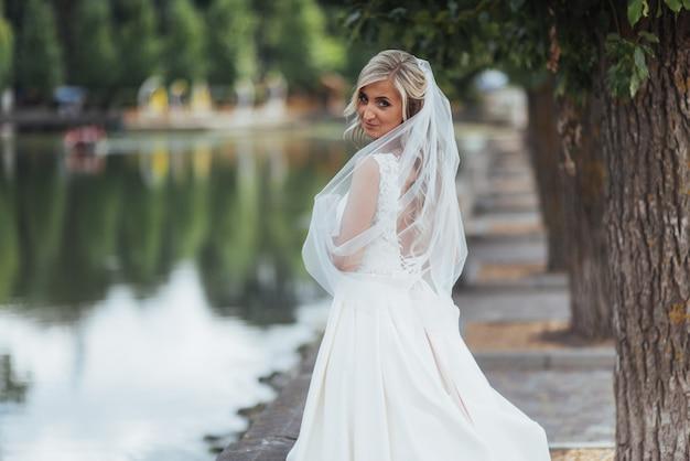 Ritratto di una sposa felice in posa con velo