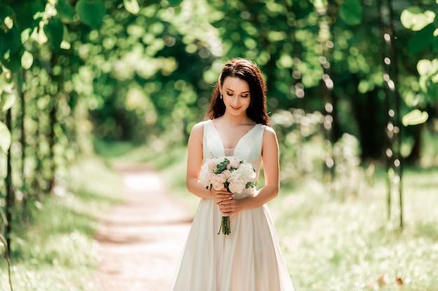 Ritratto di una sposa felice in piedi sotto un arco nel parco. eventi e tradizioni