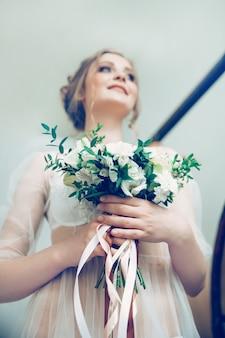 Ritratto di sposa felice con bouquet da sposa