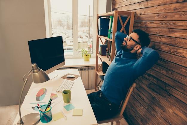 Ritratto di uomo d'affari felice che riposa dopo una lunga giornata di lavoro