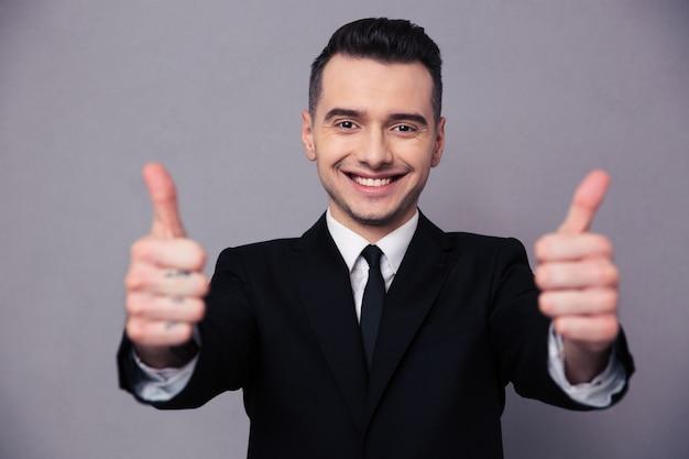Ritratto di un uomo d'affari felice che mostra i pollici in su sul muro grigio gray