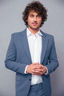 Ritratto di un uomo d'affari felice in piedi su backround grigio e guardando la parte anteriore