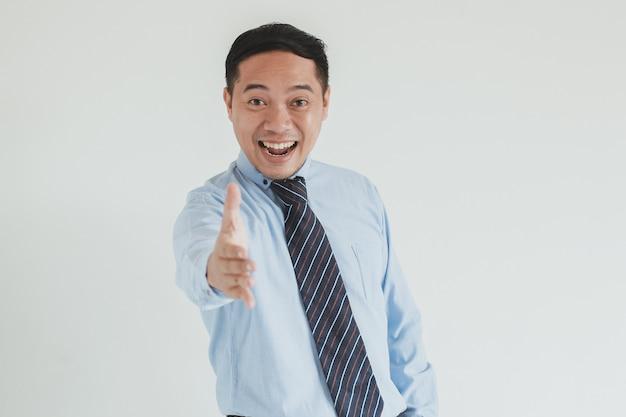 Ritratto di uomo d'affari felice che indossa camicia blu e cravatta che allunga la mano per la stretta di mano alla telecamera hands