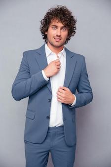 Ritratto di un uomo d'affari felice con i capelli ricci in piedi sopra il muro grigio