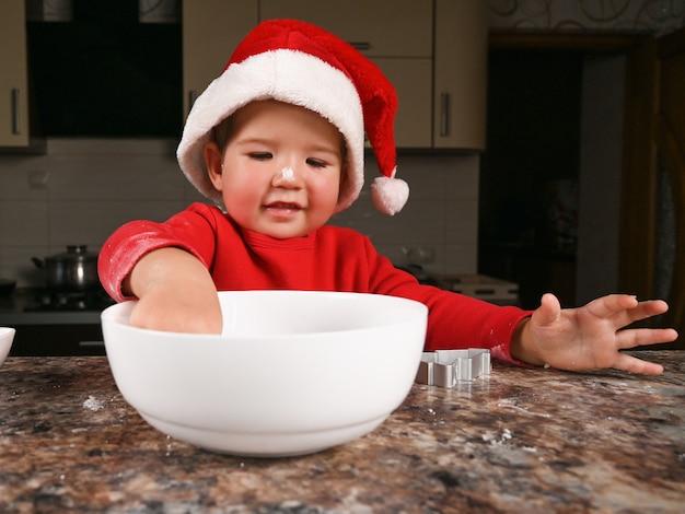 Ritratto di felice ragazzo caucasico in un cappello da babbo natale in cucina