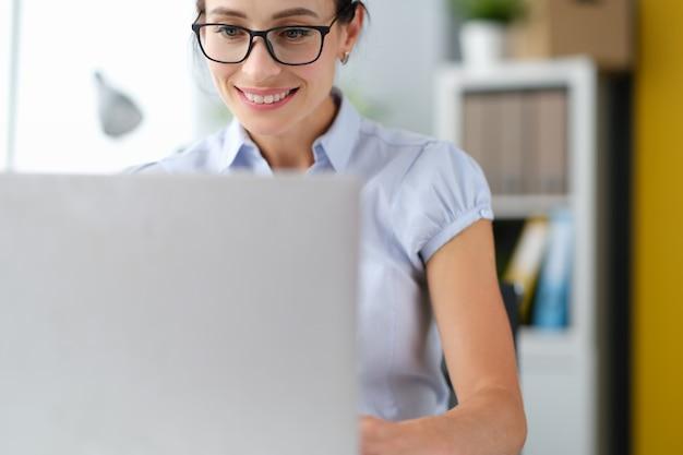 Ritratto di felice imprenditrice caucasica che lavora al computer portatile online a casa sorridente in ufficio
