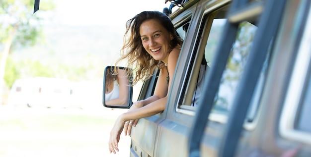 Ritratto felice donna caucasica guida un vecchio camper vintage su strada. vacanza in famiglia