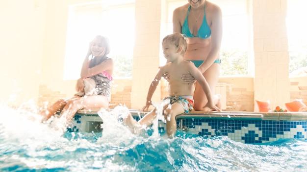 Ritratto di famiglia allegra felice seduto a bordo piscina e spruzzi d'acqua con i piedi. famiglia che gioca e si diverte in piscina