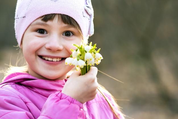 Il ritratto della ragazza felice del bambino che tiene il mazzo di bucaneve in anticipo della molla fiorisce all'aperto.