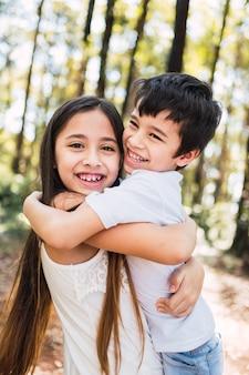 Ritratto di bambini felici che abbracciano e sorridono.