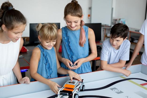 Ritratto di bambini felici a scuola in ufficio a una lezione di robotica, con un ufficio moderno con computer