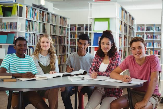 Ritratto di compagni di classe felici che studiano in biblioteca