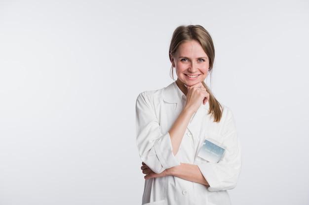 Ritratto del clinico felice che esamina macchina fotografica e che sorride con le mani attraversate