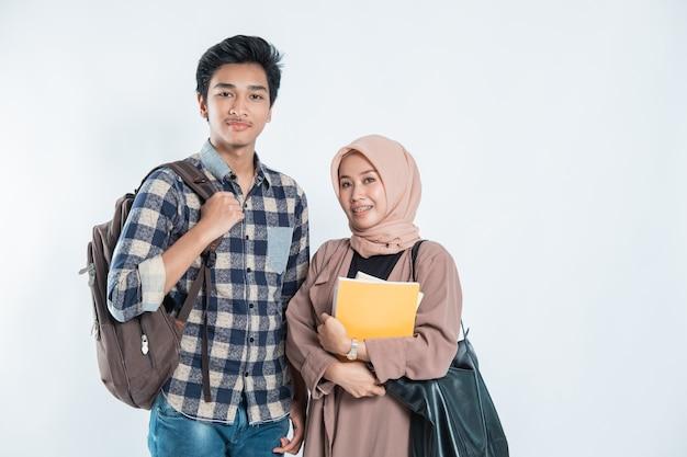 Ritratto di happy college friend portando una borsa e un libro su un bianco isolato