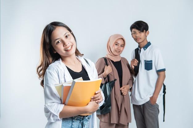 Ritratto di happy college friends portando una borsa e un libro su un bianco isolato