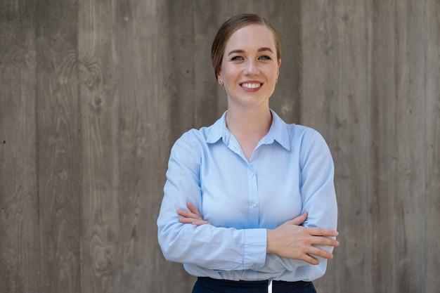 Il ritratto di giovane donna sicura di affari felice ha attraversato il braccio in città. muro grigio. goditi la vita. concetto di successo. foto di alta qualità