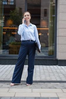 Ritratto di felice fiducioso giovane donna d'affari parlando al telefono, tenendo il computer portatile, mentre stare in città all'aperto. vita da millennial. lavora a distanza all'aperto. foto di alta qualità